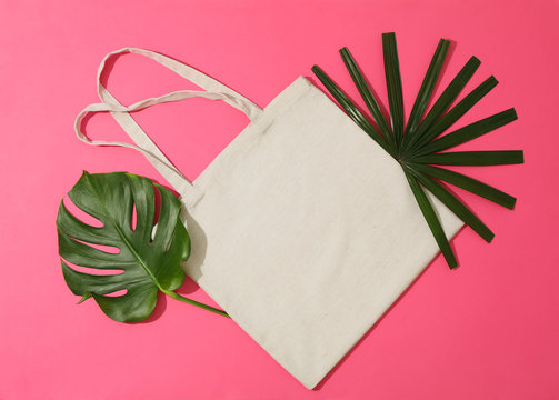 Eco bag and palm leaves on color background, top view
