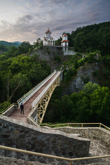 Traveller is sitting on the bridge in front of the small orthodox church on the side of the mountain in Prolom banja in southern Serbia in the early morning