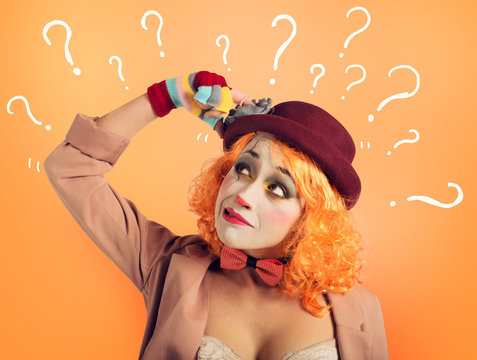 Pensive clown girl with too many questions. Orange background