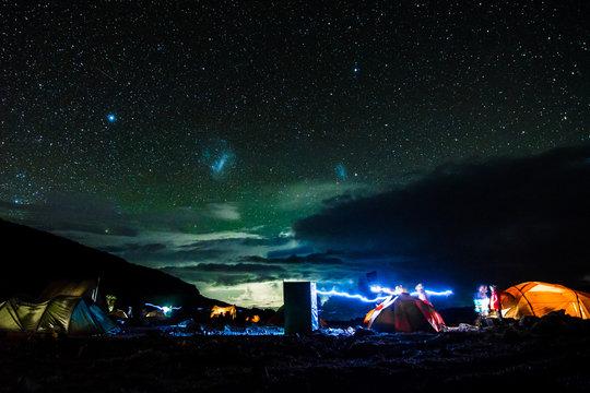 Pitched tents camping at the base of Mount Kilimanjaro at night