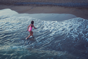 lifestyle picture of girl in pink swimsuit running on the beach