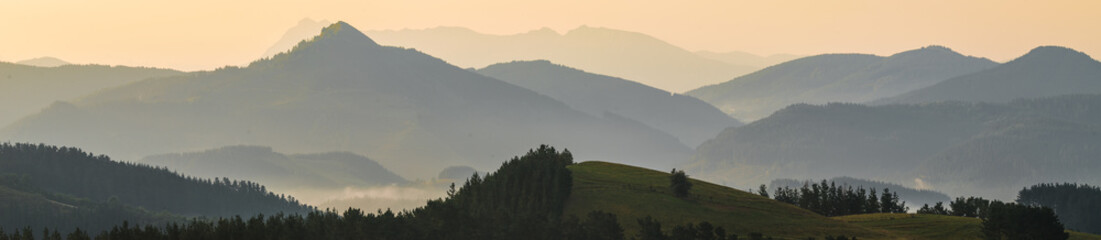 Foto op Aluminium Grijs Silhouettes of the mountains of Bizkaia from Bolibar at sunset