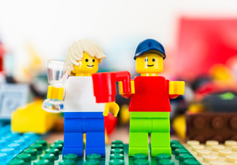 Two Lego man figures standing next to each other and holding a drink celebrating on February 15, 2019 in Poznan, Poland.