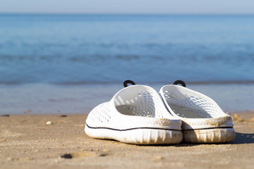 Holidays at sea. White sea slippers on the golden sand near the sea water. The best idea for a summer vacation.