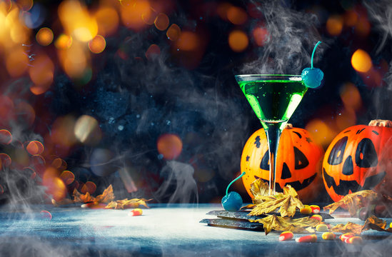 Halloween composition with festive drink, green cocktail and pumpkins lanterns, smoke and fallen leaves on night dark blue background, selective focus