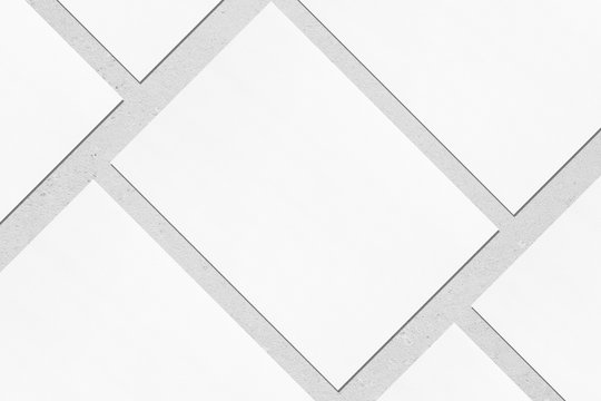 Closeup of empty white rectangle poster mockups lying diagonally with soft shadow on neutral light grey concrete background. Flat lay, top view. Open composition.