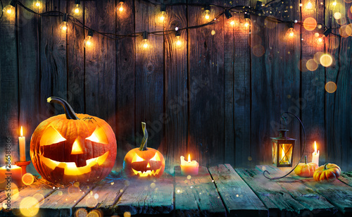 Halloween - Jack O' Lanterns - Candles And String Lights On Wooden Table