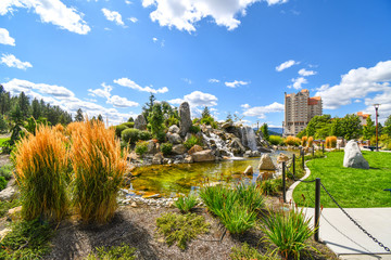 A large pond with waterfall inside the public McEuen Park near resorts and Tubbs Hill in the lakefront town of Coeur d'Alene, Idaho.