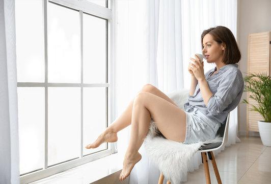 Morning of beautiful young woman drinking coffee near window