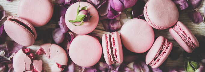 Flat-lay of sweet pink macaron cookies and rose buds and petals over wooden background, top view, close-up, wide composition. Food texture, background and wallpaper Wall mural