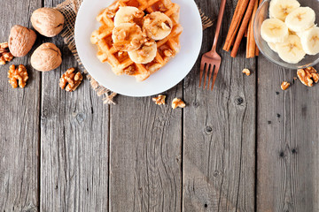 Breakfast waffle with bananas, walnuts and syrup. Above view top border with copy space over a wood background.