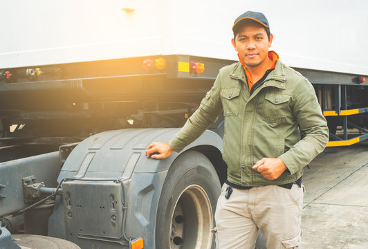 Portrait of Asian a truck driver with semi truck trailer.