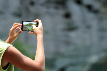 Travelers using Mobile phone and cameras take picture of mountains and lakes