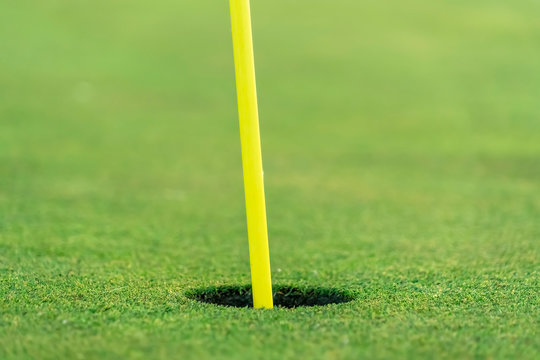 Close up view of the yellow pin and cup of a golf course on a sunny day