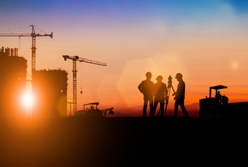 Silhouette of Survey Engineer and construction team working at site over blurred  industry background with Light fair.Create from multiple reference images together