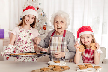 Grandmother with granddaughters baking cookies