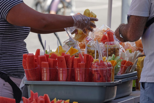 A food vendor sells fruit on a sidewalk in Los Angeles during a summer day.