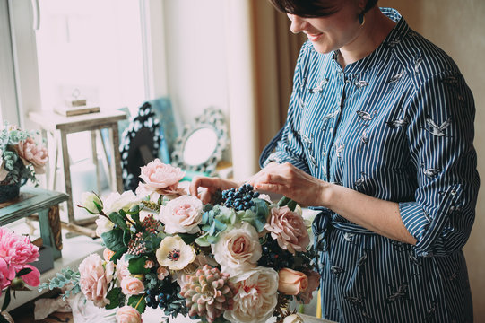 Small business. Florist girl creates a flower arrangement in her decor studio. Hands close-up