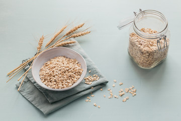 Bowl of dry oat flakes with ears of wheat on light blue background.