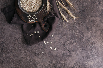 Bowl of dry oat flakes with ears of wheat on dark background. Cooking oats porridge concept.