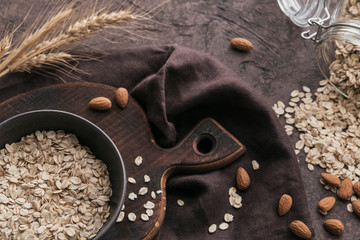 Bowl of dry oat flakes with ears of wheat and almond nuts on dark background.