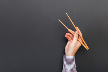 Creative image of wooden chopsticks in male hands on black background. Japanese and chinese food with copy space