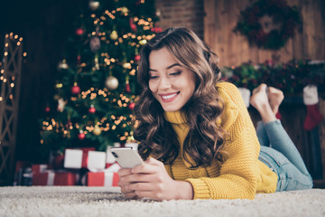 Low below angle view photo of charming cute beautiful attractive girlfriend browsing through her phone in search of something while wearing jeans denim yellow sweater