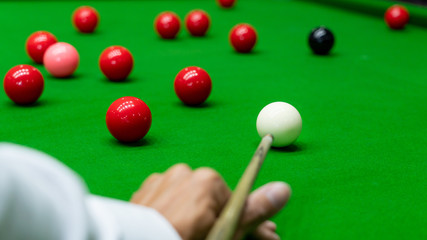 Game snooker billiards or opening frame player ready for the ball shot, athlete man kick cue on the green table in bar.
