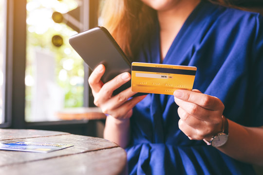 Closeup image of asian woman using credit card for purchasing and shopping online on mobile phone