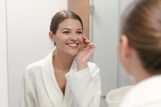 Woman in bathrobe looking in mirror at bathroom