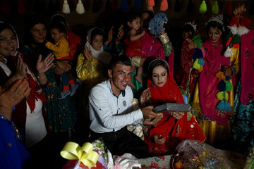 Sahar and Zal Shahbazi, Iranian nomad bride and groom, hold the Koran during their traditional wedding at Bazoft town in Chaharmahal and Bakhtiari Province