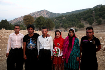 Sahar and Zal Shahbazi, Iranian nomad bride and groom, pose for a photo with their friends during their traditional wedding at Bazoft town in Chaharmahal and Bakhtiari Province