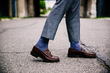 Selective closeup shot of a person wearing blue pants and brown shoes with blue socks