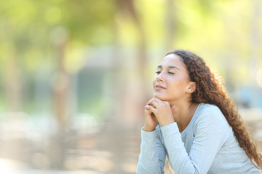 Mixed-race woman relaxing meditating in a park