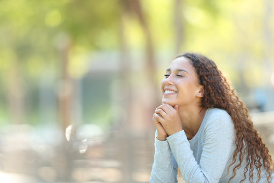 Happy mixed-race woman meditating in a park