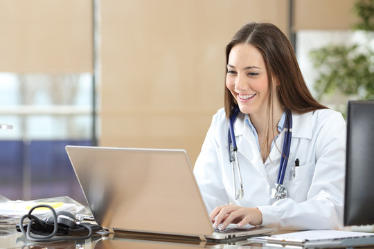 Happy doctor using a laptop at consultation