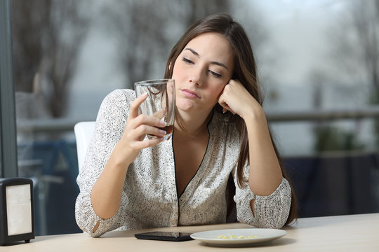 Worried pensive woman looking at glass in a coffee shop