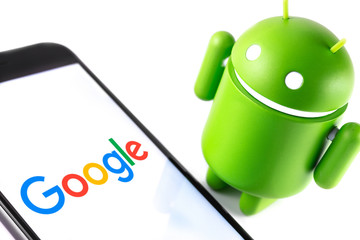 Google Android figure and smartphone with Google logo. Google Android is the operating system for smartphones, tablet computers and other devices. Moscow, Russia - March 17, 2019