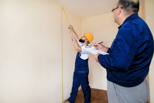 Engineer, contractor and project manager with his colleague, construction worker, handyman and builder is measuring wall of room for renovation using measure tape and checking in apartment blueprint.