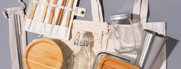 Cotton bags, glass jar, bottle, metal cup, straws for drinking, bamboo cutlery and boxes on gray...