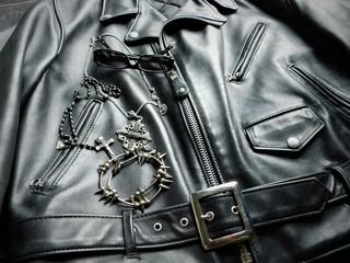 Blouson de cuir, lunettes noires et bijoux pour un rocker.