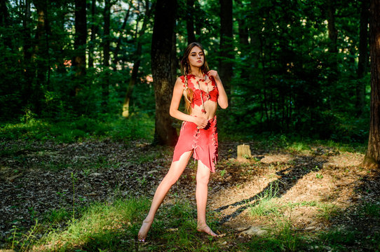 Perfect body in sexy costume. sexy girl in leather clothes. ethnic tribal fashion. deep forest. amazon woman. sexy witch. cougar female. wild woman in forest. wild amazon in deep forest