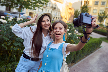 Two girls take a selfie in the park.