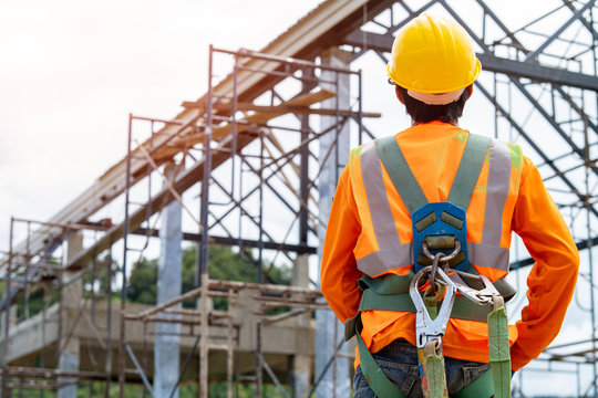 Construction worker wearing safety harness and safety line working at high place,Practices of occupational safety and health can use hazard controls and interventions to mitigate workplace hazards.