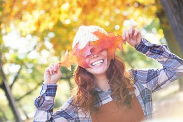 Junge schöne rothaarige Frau mit Locken und Blättern vor den Augen