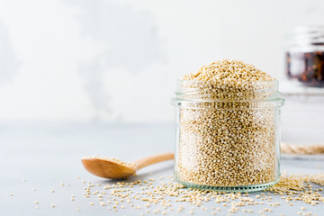 Raw quinoa grains in jar. Healthy vegetarian food on gray kitchen table. Selective focus.