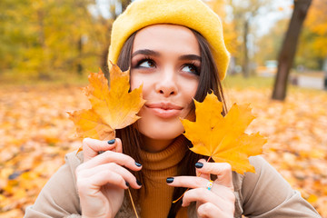 Autumn woman in autumn park. Warm sunny weather. Fall concept.A beautiful female dreaming in the autumn park. Wall mural