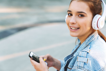 Image closeup of lovely smiling girl listening music with cellphone and headphones while sitting on sports ground
