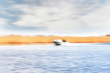 Fotobehang - An abstract blurred out of focus image of a boat racing at speed along a river.