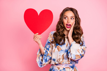 Portrait of her she nice-looking attractive lovely fascinating amazed cheerful cheery glad wavy-haired girl holding in hand large big healthy heart life lifestyle dream isolated over pink background
